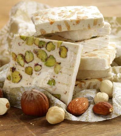 nougat blanc avec différentes noix sur une table en bois Banque d'images