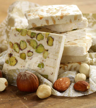 white nougat with different nuts on a wooden table Imagens