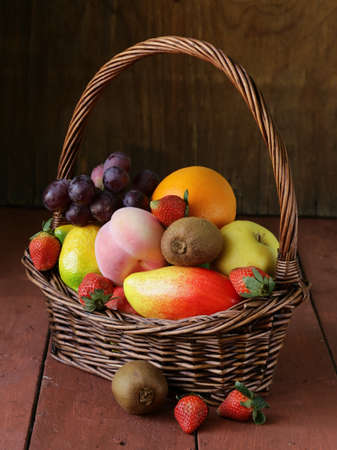 still life wicker basket with fruit on a wooden table photo