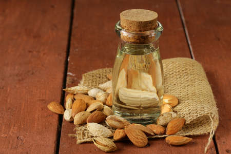 almond oil in a glass bottle with whole nuts photo