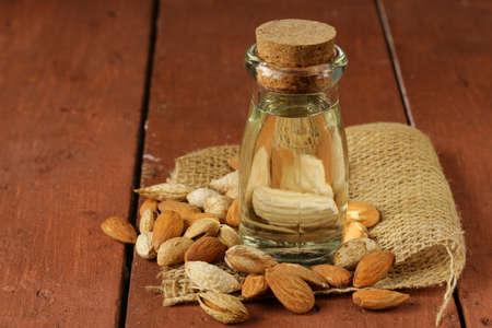 l'huile d'amande dans une bouteille en verre avec des noix entières Banque d'images