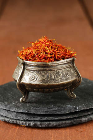 Saffron spice in metal bowl macro shot soft focus photo