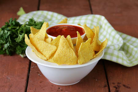 corn tortilla: corn tortilla chips in a bowl with tomato sauce Stock Photo