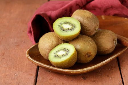 raw food: tropical fruit fresh sweet ripe kiwi on wooden plate