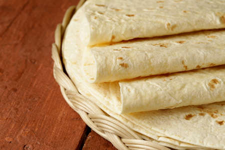 tortillas: stack of homemade whole wheat flour tortillas on a wooden table