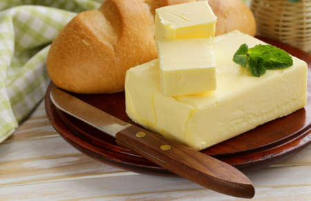 piece of fresh butter for breakfast on a wooden board photo