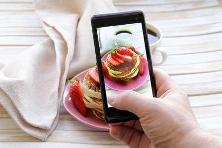 Smartphone geschossen Essen Foto - Pfannkuchen zum Frühstück mit frischen Erdbeeren Lizenzfreie Bilder