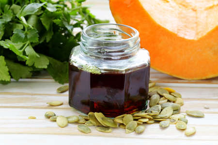 organic pumpkin oil in a glass jar on a wooden table