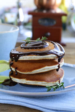 homemade pancakes with chocolate syrup and thyme photo