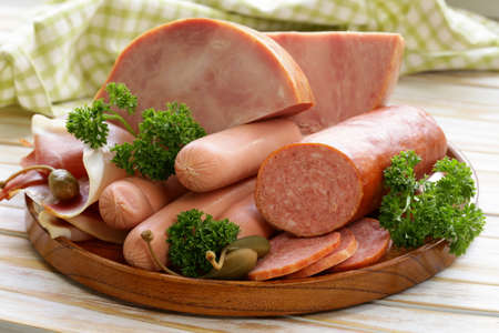 various kinds of sausages and smoked bacon on the wooden plate Imagens