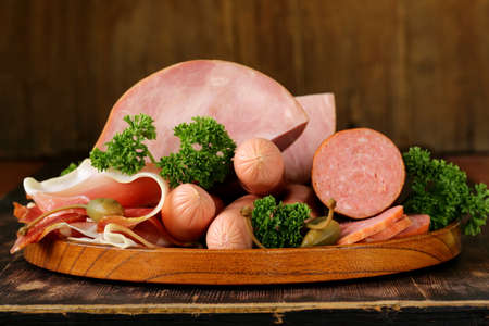 various kinds of sausages and smoked bacon on the wooden plate Banque d'images
