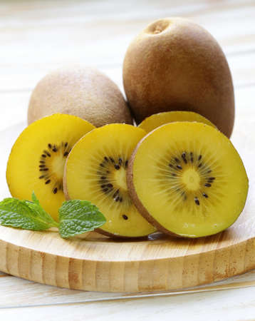 ripe yellow kiwi on a wooden board Imagens