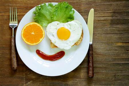 Cara divertida de servir el desayuno, huevo frito, tostadas y ensalada verde Foto de archivo - 28759528