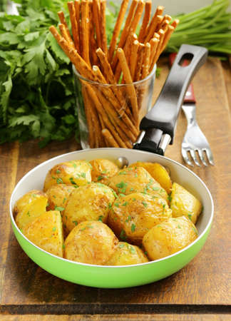 tasty baked potatoes with herbs in the pan photo