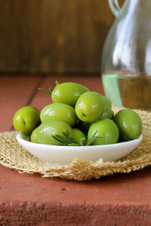 green marinated olives in bowl on a wooden table photo