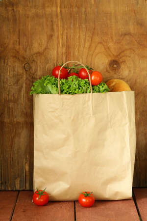 paper bag with food, lettuce, tomatoes, bread on a wooden background photo