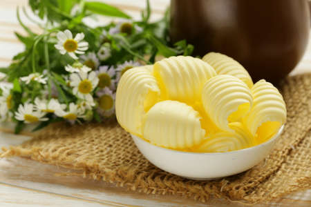 butterfat: fresh yellow dairy butter in a white bowl