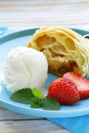 traditional apple strudel with raisins, served with a scoop of ice cream photo