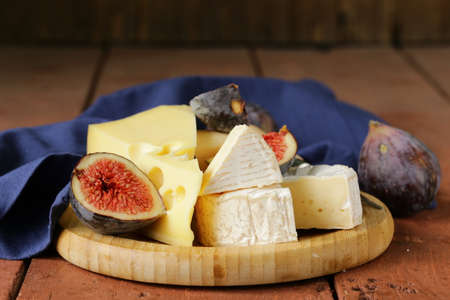 cheeseboard: cheeseboard with maasdam, camembert, cheddar cheese and figs Stock Photo