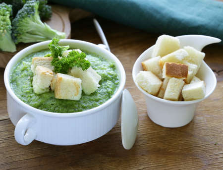 vegetable broccoli cream soup with white croutons and parsley photo