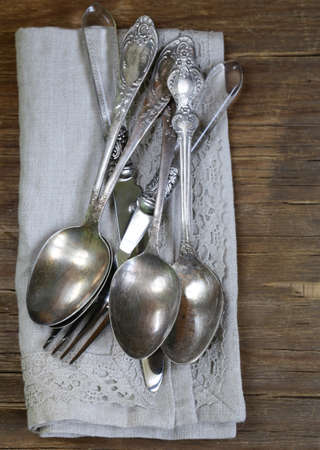 grunge silverware: vintage silver cutlery with linen napkin on wooden background Stock Photo