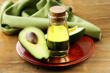 oil of avocado and fresh fruit on wooden table photo