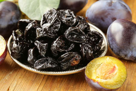 Dried plums prunes and fresh berries on the wooden table