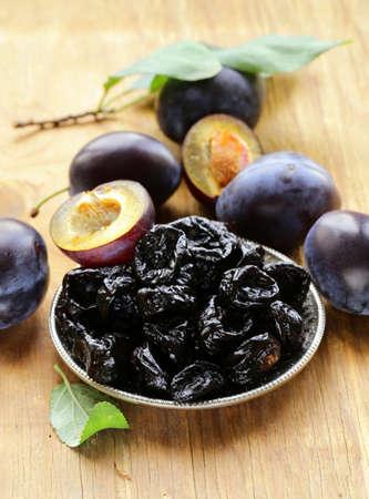 frutas deshidratadas: Secos ciruelas pasas y las bayas frescas en la mesa de madera