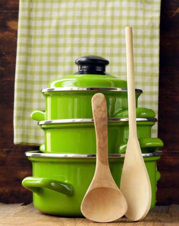 utensilios de cocina: juego de ollas de metal verde recipiente sobre un fondo de madera Foto de archivo