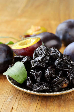 Dried plums prunes and fresh berries on the wooden table photo