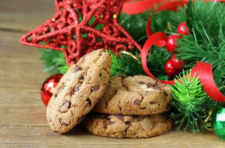 galletas de jengibre: galletas con chocolate en un fondo de madera con ramas y decoraciones para �rboles de Navidad