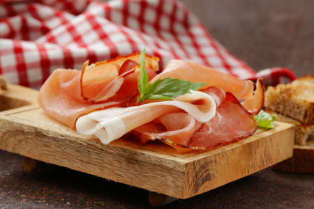smoked ham jamon (Parma) with basil leaves on a wooden board Banco de Imagens