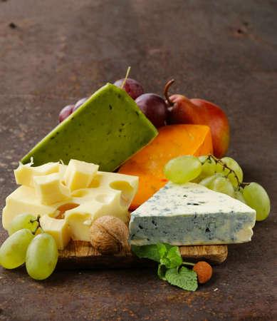 tabla de quesos: tabla de quesos con diferentes tipos de queso y uvas Foto de archivo