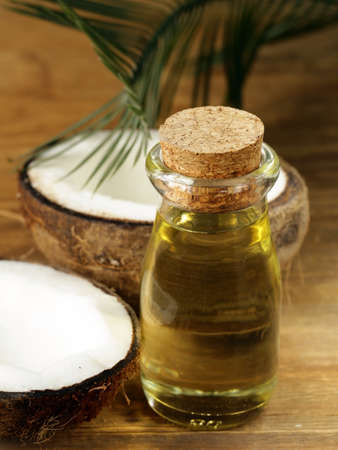coconut leaf: coconut oil in a glass bottle and fresh nuts Stock Photo