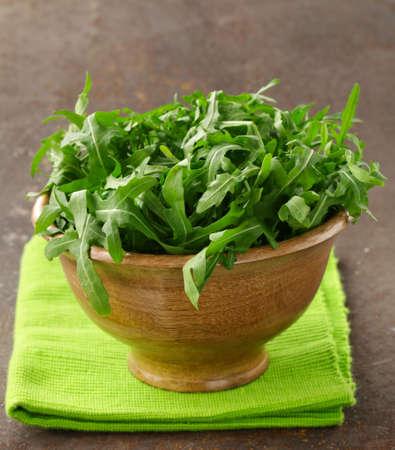 rukola: fresh green salad arugula in a wooden bowl Stock Photo