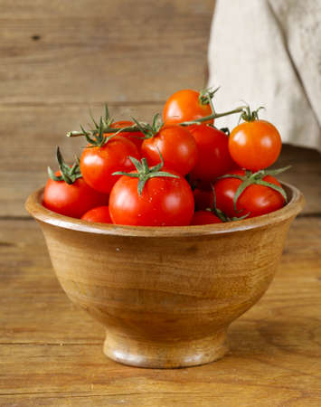 Fresh ripe red tomatoes in a wooden bowl
