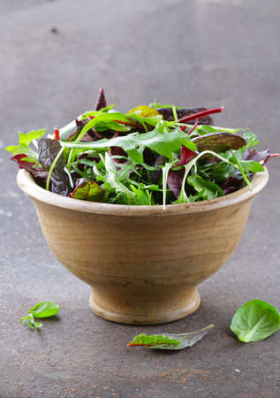 roquette: mix salad (arugula, iceberg, red beet) in a wooden bowl Stock Photo