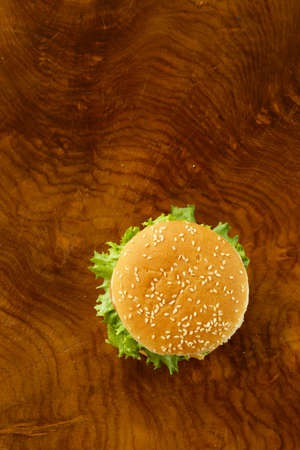 burger: traditional cheeseburger with green lettuce and tomatoes on a wooden background Stock Photo
