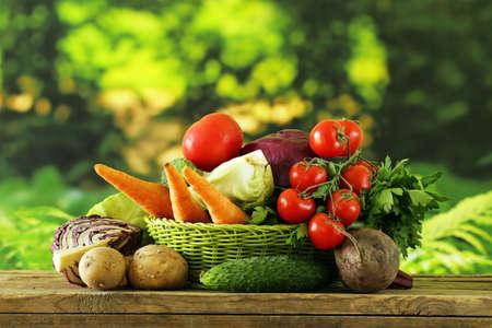 verduras verdes: varias verduras (zanahorias, papas, repollo, tomates) en la cesta Foto de archivo