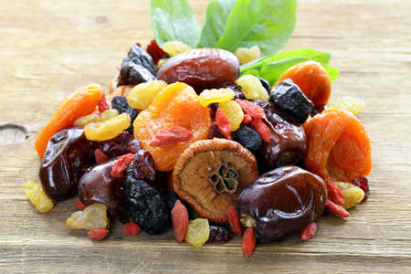 frutas secas: Surtido de frutas secas pasas albaricoques higos ciruelas arándanos goji sobre un fondo de madera