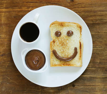 breakfast smiley face: Breakfast serving funny face on the plate toast chocolate spread and coffee