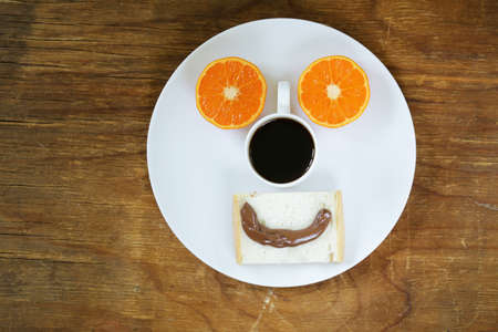 breakfast smiley face: Breakfast serving funny face on the plate toast chocolate spread and orange
