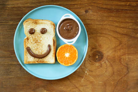 spreading: Breakfast serving funny face on the plate toast chocolate spread and orange