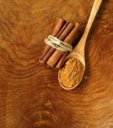 christmas grounds: fragrant cinnamon sticks and ground spices on a wooden background Stock Photo