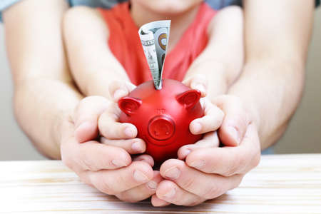 son deposit: close up of father and son hands holding red piggy bank Stock Photo
