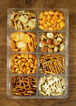 Various salty snacks  crackers chips nuts pretzels Stock Photo