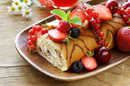 roulade: biscuit roulade with butter cream and fresh berries Stock Photo
