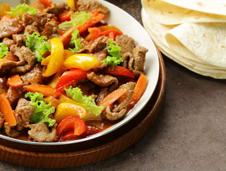 mexican food: Beef Fajitas with colorful bell peppers in pan on a wooden table
