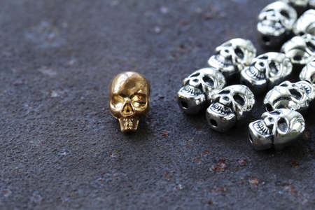 gold metal: Gold unique skull among ordinary metal skulls Stock Photo