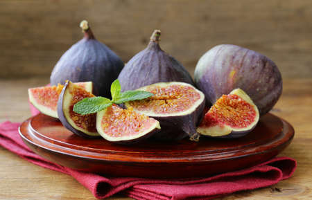 purple fig: fresh organic purple fig fruit on wooden plate